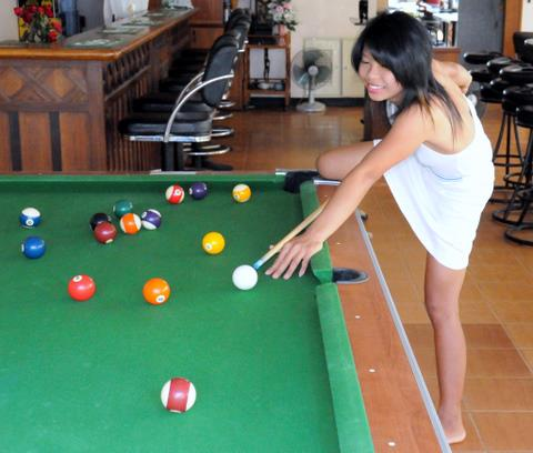 Sexy bar girl playing pool