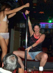 Drunk farang lady pole-dancing in a GoGo bar at Jomtien